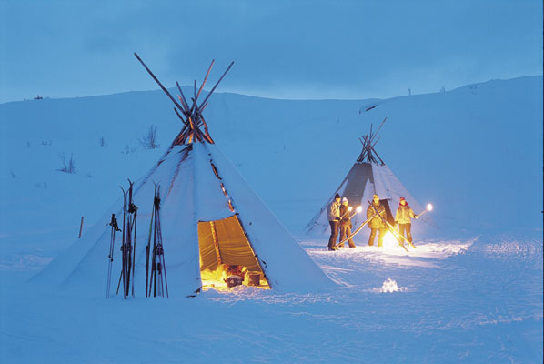 Valdres nigth evening tents with fire wigwam in snow people with fire mountain fire at nigth, Norwegen